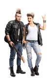 Male punker with a guitar and a female punker. Full length portrait of a male punker with a guitar and a female punker making a rock sign isolated on white royalty free stock photography