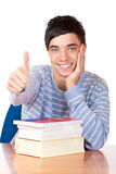 Male pupil with books and shows thumb up. Happy pupil sitting on desk with books and shows thumb. Isolated on white background Royalty Free Stock Photos