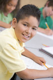 Male pupil in elementary school classroom. Writing at desk Royalty Free Stock Image