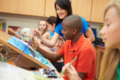 Male Pupil In High School Art Class With Teacher. Having A Conversation royalty free stock photo