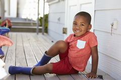 Male Pupil At Montessori School Putting On Wellington Boots stock photo