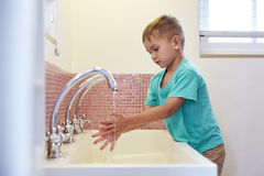 Male Pupil At Montessori School Washing Hands In Washroom Royalty Free Stock Image