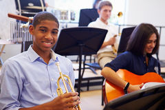 Male Pupil Playing Trumpet In High School Orchestra. Sitting Down Smiling At Camera Royalty Free Stock Images
