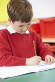 Male Pupil Practising Writing At Table Royalty Free Stock Photography