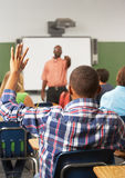 Male Pupil Raising Hand In Class. Answering Question Sitting Down Royalty Free Stock Photos