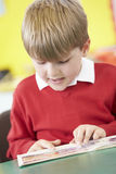 Male Pupil Reading Book At Table Stock Photos