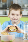 Male Pupil Sitting At Table In School Cafeteria Eating Healthy P Royalty Free Stock Image