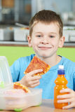 Male Pupil Sitting At Table In School Cafeteria Eating Unhealthy. Male Pupil Sits At Table In School Cafeteria Eating Unhealthy Packed Lunch Stock Images
