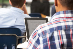Male Pupil Using Digital Tablet In Classroom. Sitting Down Wearing Checkered Shirt Stock Images