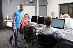 Male Pupil Walking On Crutches In Computer Class Royalty Free Stock Images
