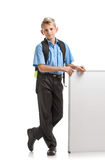 Male pupil with whiteboard. Modern male pupil with schoolbag standing near whiteboard Royalty Free Stock Image
