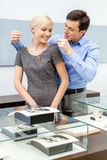 Male puts necklace on his girlfriend. At jeweler's shop. Concept of wealth and luxurious life stock image