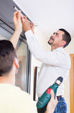 Male putting corbel at kitchen. Two male serious putting corbel at residential kitchen stock photography