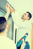 Male putting corbel at kitchen. Two male serious putting corbel at residential kitchen royalty free stock photos