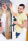 Male putting corbel at kitchen. Two male young putting corbel at residential kitchen stock image