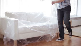 Male putting down new sofa at home