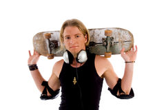 Male putting skateboard on shoulders Royalty Free Stock Images