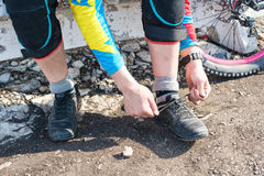 Male racer mtb cyclist preparing for race tying shoelaces stock photos