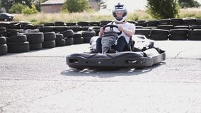 Male racer in protective helmet racing on the go-kart track outdoors. Attractive male racer in protective helmet racing on the go-kart track outdoors stock video
