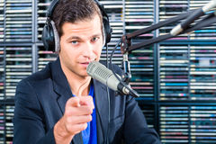 Male radio presenter in radio station on air. Male Presenter in radio station hosting show for radio live in Studio royalty free stock images