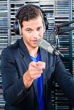 Male radio presenter in radio station on air. Male Presenter in radio station hosting show for radio live in Studio Stock Images
