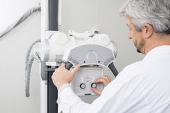 Male Radiologist Adjusting The Controls On X-ray Machine Stock Images
