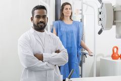 Male Radiologist Standing Arms Crossed In Examination Room. Young male radiologist standing arms crossed with female patient in background at examination room Stock Photos