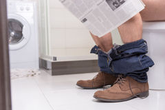 Male reading newspaper while sitting on the toilet seat. Male wearing jeans and shoes reading newspaper while sitting on the toilet seat in the modern tiled Stock Images