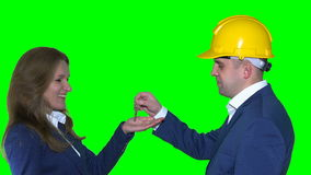 Male real estate agent giving house keys to female customer stock footage