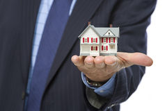 Male Real Estate Agent Holding Miniature House in Palm. Close Up of Male Real Estate Agent Holding Out A Miniature House in His Hand Royalty Free Stock Photography