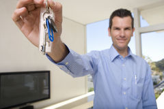 Male real estate agent holding up keys in living room, smiling, portrait (focus on keys) royalty free stock image