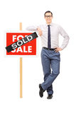 Male real estate agent leaning on a sold sign Stock Photos