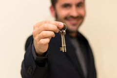 Male real estate agent smiling while handing over keys. After a successful sale Royalty Free Stock Image
