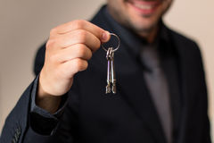 Male real estate agent smiling while handing over keys. After a successful sale Stock Images