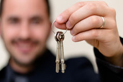 Male real estate agent smiling while handing over keys. After a successful sale Royalty Free Stock Photography
