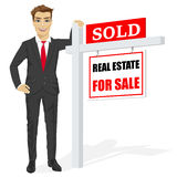 Male real estate agent standing next to a sold for sale sign Stock Photos
