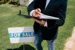 Real estate agent standing by signboard Stock Image