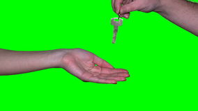 Male real estate realtor seller woman give apartment key to female customer hand. Isolated on green even chroma key background. Static closeup shot. 4K UHD stock video footage