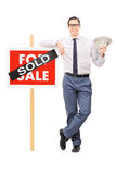 Male realtor holding money next to a sold sign. Isolated on white background stock photo