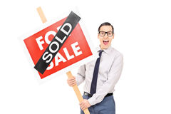 Male realtor holding a sold sign Royalty Free Stock Images
