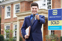 Male Realtor Standing Outside Residential Property Holding Keys Stock Photography