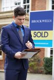 Male Realtor Standing Outside Residential Property With Sold Sig stock photo