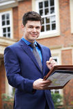Male Realtor Standing Outside Residential Property Stock Image
