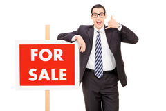 Male realtor standing by a for sale sign Royalty Free Stock Photography