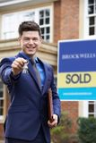 Male Realtor Standing Outside Residential Property Holding Keys stock image