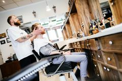 Male receiving hair beard treatment. In barber shop stock images