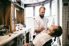 Male receiving hair beard treatment. In barber shop stock photo