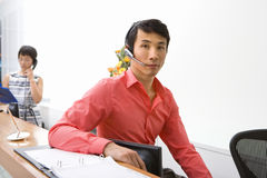 Male receptionist by desk, colleague on telephone in background, portrait Stock Images
