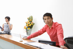 Male receptionist leaning on desk, colleague in background, portrait Royalty Free Stock Photography