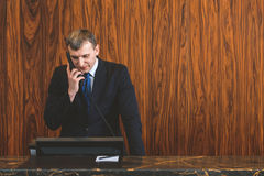 Male receptionist talking on phone with guest. We always looking forward to your arrival. Adult clerk standing at reception desk and making reserve while holding Stock Images
